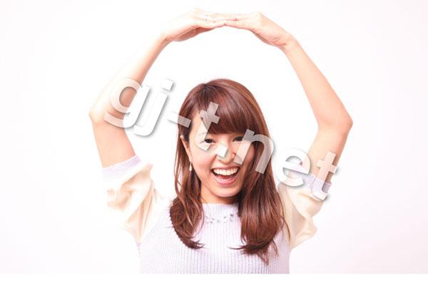 頭の上で丸をつくる笑顔の女性