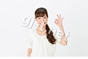 okサインをする白い服の女性