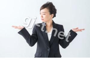 両手で比べるスーツの女性