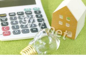電球と家の模型と電卓