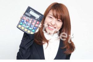 笑顔で電卓を持つスーツの女性