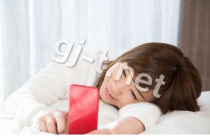 寝ながらスマホを笑顔で見る女性