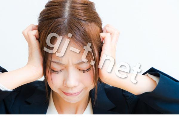 頭を抱えるスーツの女性