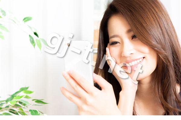 スマホを見て笑顔になる女性