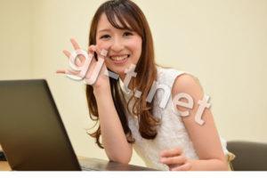 パソコンの前でokサインをする女性