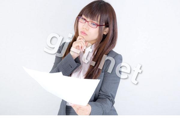 書類を見て悩む赤メガネでグレーのスーツの女性